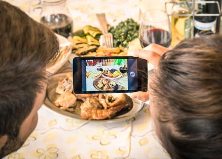 food on table: Coppia di ragazzo e ragazza prendendo un selfie cibo nel ristorante cena - Moda di catturare l'istante con lo smartphone moderno alla riunione pranzo con cucina tipica italiana