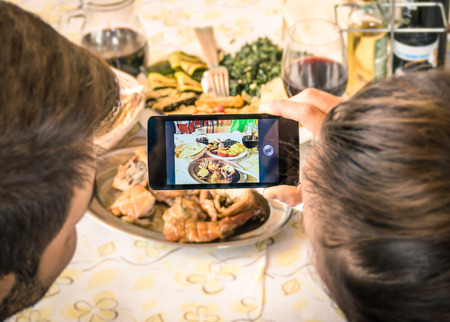 Couple of boyfriend and girlfriend taking a food selfie in dinner restaurant - Moda of catching the instant with modern smartphone at lunch meeting with typical italian food