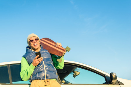 Young hipster man with smartphone listening music next his car - Concept of modern technologies mixed with a vintage travel lifestyle - Autumn winter youth alternative fashion in a sunny day trip photo
