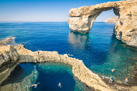 The world famous Azure Window in Gozo island - Mediterranean nature wonder in the beautiful Malta - Unrecognizable touristic scuba divers 免版税图像 - 32657345