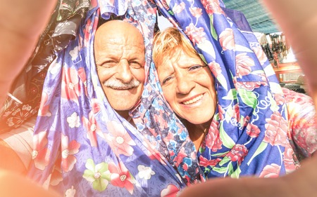 Senior happy couple taking a selfie at the week clothes market traveling around the world - Concept of active elderly and interaction with new technologies and trends photo