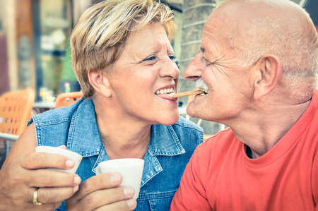 Happy playful senior couple in love tenderly enjoying a cup of coffee - Joyful elderly active lifestyle - Man having fun and smiling with her wife in a bar cafe restaurant during vacation photo