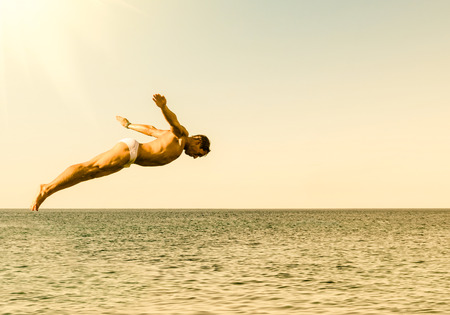 free diving: Cliff diver jumping in the sea against the sky at sunset - Concept of freedom and carefree sensation feeling the pure connection with the nature