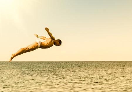 Diver Cliff sauter dans la mer sur le ciel au coucher du soleil - Concept de la liberté et de la sensation insouciante sentir la connexion pur avec la nature
