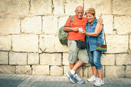 tercera edad: Mayor feliz pareja que se divierten con un tel�fono inteligente moderno - Concepto de ancianos activos y la interacci�n con las nuevas tecnolog�as - el estilo de vida de viajes sin l�mite de edad Foto de archivo