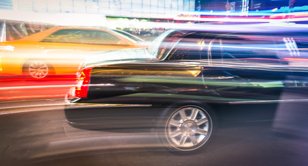 Speeding car and yellow taxi cab in a blurred night - Traffic jam in New York City - Times Square Manhattan downtown