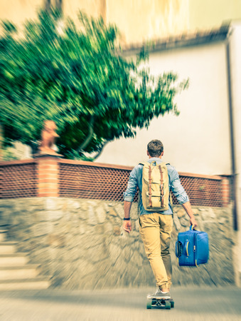 vagabond: Young hipster man moving forward with his longboard holding his trolley backpack - Modern concept of freedom and alternative lifestyle - Cheap travel backpacking around the world Stock Photo