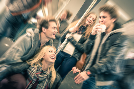 Group of young hipster friends having fun interaction and talking in subway train - Vintage filtered look with radial defocusing - Concept of youth and friendship