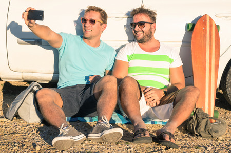 Travel Backpack: J�venes mejores amigos que toman un inconformista Autofoto sentado al lado del coche Foto de archivo