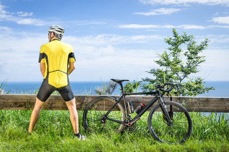 urinating: Cyclist peeing in the bushes during a Race Stock Photo