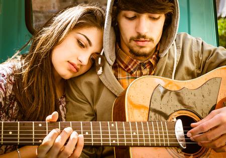 parejas romanticas: Joven pareja romántica que toca la guitarra al aire libre después de la lluvia Foto de archivo
