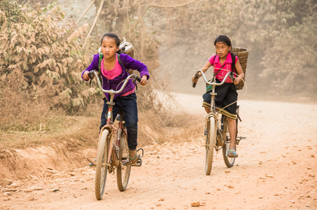 ANG VIENG, LAOS - JANUARY 26: young unidentified girls cycling back from school on a dusty road on January 26, 2013 in Vang Vieng, Laos. Around the villages there are more kids than adults