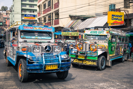 cheapest: BAGUIO, PHILIPPINES - FEBRUARY 4, 2014: colorful jeepneys at the bus station of the city of Baguio. Inspired from US military jeeps, those are the cheapest and kitschest transportation in the country. Editorial