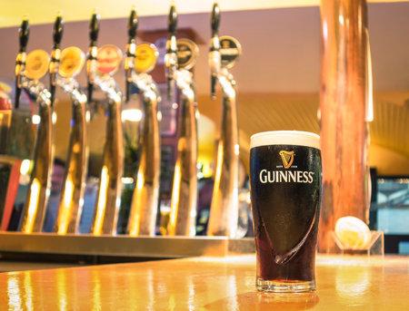 cerveza negra: Rimini, Italia - 11 de octubre 2014: pinta de cerveza servida en un pub. Guinness es un dry stout irlandesa famosa mundo creado en la fábrica de cerveza de Arthur Guinness (17251803) en St. James