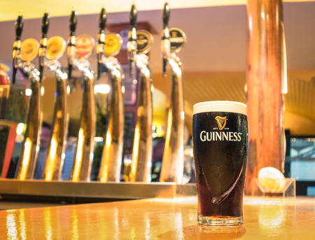 dublin: RIMINI, ITALY - OCTOBER 11, 2014: pint of beer served in a pub. Guinness is a world famous Irish dry stout created in the brewery of Arthur Guinness (1725�1803) at St. James