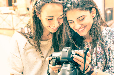 smiling teenagers: Young girls watching photos in a digital Camera