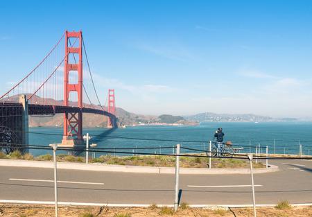 unidentified: Golden Gate en San Francisco - Camino de la bicicleta y del motorista no identificado de tomar una fotograf�a Foto de archivo
