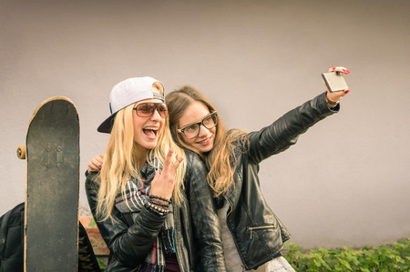 longboard: Hipster girlfriends taking a selfie in urban city context - Concept of friendship and fun with new trends and technology - Best friends eternalizing the moment with modern smartphone