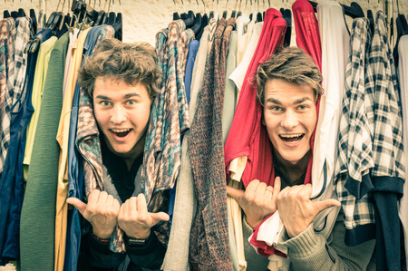 vintage clothes: Young hipster brothers at the weekly cloth market - Best friends sharing free time having fun and shopping in the old town in a sunny day - Guys enjoying everyday life moments