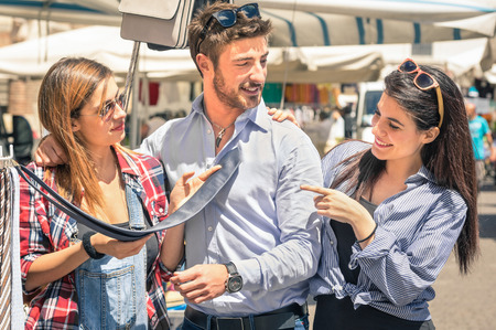 Young tourists at the weekly cloth market - Best friends sharing free time on the weekend having fun and shopping in the old town - Male tie casual fashion photo