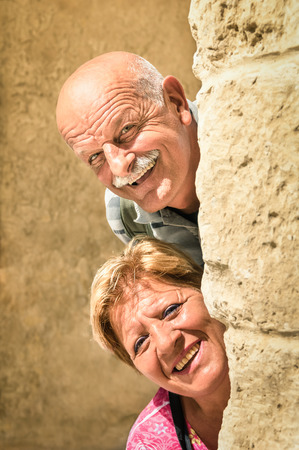 'hide out': Happy senior couple in love during retirement - Joyful elderly lifestyle with man and woman with funny playful attitude - Visiting the old town during a sightseeing tour