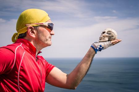 Cyclist with bandana Headband looking at a Skull Stock Photo