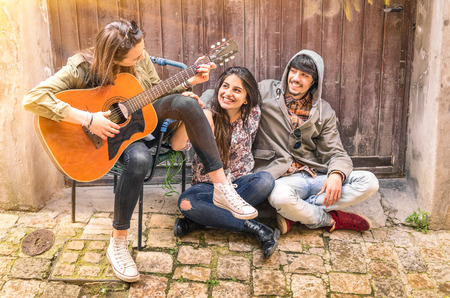 best location: Group young of best friends playing guitar outdoors on a grungy location Stock Photo