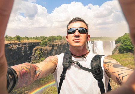 Modern hipster young man taking a selfie at Victoria Waterfalls - Adventure travel lifestyle enjoying moment of connection with nature - Trip excursion in Africa Zimbabwe nature wonder destination