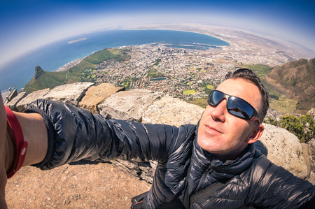 Modern handsome young man taking a selfie at Table Mountain in Cape Town - Adventure travel lifestyle enjoying connection with nature - Trip excursion in South Africa at nature wonder destination photo