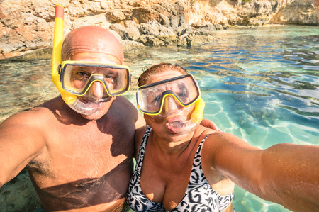 Senior happy couple taking a selfie at Blue Lagoon in Gozo and Comino - Travel to mediterranean island of Malta - Concept of active elderly and fun around the world experimenting new technologies 스톡 콘텐츠