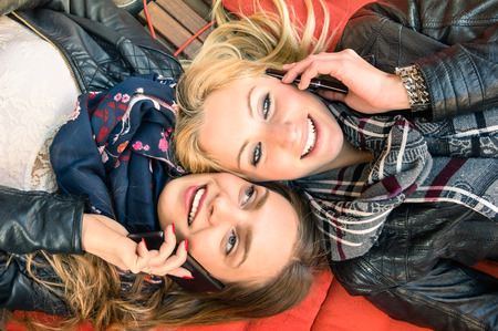 Best friends enjoying time together outdoors with smartphone - Concept of new technology with two girlfriends having fun on a vintage wood bench and red pillows