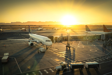 Airplane at the terminal gate ready for takeoff - Modern international airport during sunset - Concept of emotional travel around the world Éditoriale