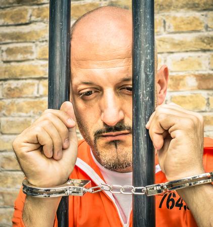 handcufs: Dead Man Walking - Sad Prisoner with Handcuffs behind Bars