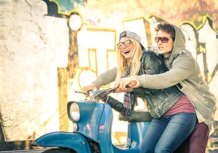Joven pareja de amantes haviing diversión en un ciclomotor scooter de la vendimia - Hermoso hombre en actitud lúdica con su bella novia - A partir de una historia de amor en un día soleado de invierno cálido Foto de archivo