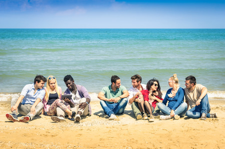 multi race: roup of international best friends sitting at beach talking with each other - Concept of multi cultural friendship against racism - Interaction with new technologies tablet and contact with nature Stock Photo