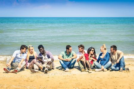personas reunidas: rupo de los mejores amigos internacionales que se sientan en la playa hablando entre s� - Concepto de m�ltiples amistad cultural contra el racismo - La interacci�n con las nuevas tecnolog�as de la tableta y el contacto con la naturaleza