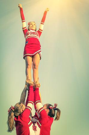 competencia: Cheerleaders en acci�n en una mirada filtrada vendimia - Concepto de unidad y deporte de equipo - Capacitaci�n en la universidad de la escuela secundaria con j�venes adolescentes mujeres Foto de archivo
