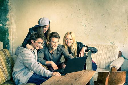 Groep jonge hipster beste vrienden met laptop in stedelijke alternatieve locatie - concept van vriendschap en plezier met nieuwe trends en technologie - Draadloze verbinding en web internet interactie Stockfoto