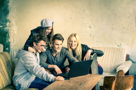 Group of young hipster best friends with computer laptop in urban alternative location - Concept of friendship and fun with new trends and technology - Wireless connection and web internet interaction