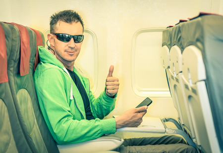 Young hipster man passenger satisfied with thumbs up after boarding - Concept of low coast flight and connection with modern technologies on board - Alternative lifestyle traveling around the world
