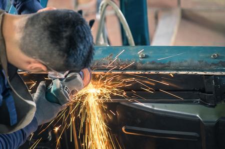 molinillo: Joven trabajador mecánico de reparación de un cuerpo de coches de época antigua en el garaje desordenado - Seguridad en el trabajo con el desgaste de protección