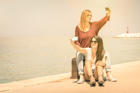 eternal life: Hipster girlfriends taking a double selfie at wharf docks - Concept of friendship and fun with new trends and technology - Best friends fixing the moment with modern smartphone Stock Photo