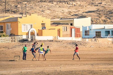 Luderitz, Namibië - 24 november 2014: de lokale jongeren voetballen in de speeltuin naast een moderne township; voor geluk en getalenteerde spelers, voetbal is een snelle manier om de armoede van sloppenwijken te ontsnappen