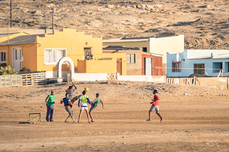 LUDERITZ, NAMIBIA - 24 NOVEMBER 2014: local young people playing football in the playground next to a modern township; for lucky and talented players, soccer is a fast way to escape poverty of slums Stock Photo - 34289240
