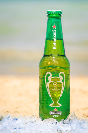 international beer: RIMINI, ITALY - MAY 18, 2014: Heineken bottle at the beach ready to drink. Heineken Lager Beer is produced by the Dutch brewing company Heineken International and exported all over the world