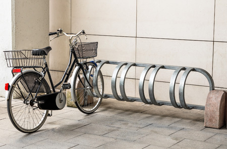 a two wheeled vehicle: Bicycle ready for use in urban area - Bike rack in city commercial center