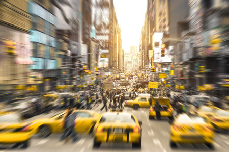 Rush hour with yellow taxi cabs and melting pot people on 7th av. in Manhattan downtown before sunset - Bright blurred defocused postcard of New York City and his crowded traffic jam