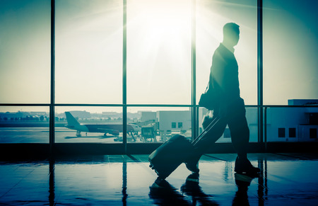 airport business: Business man at international airport with suitcase Stock Photo