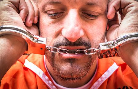 handcufs: Sad Man with Handcuffs in Prison Stock Photo