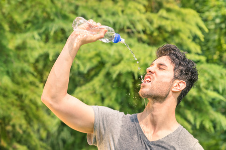 dehydrated: Sporty man refreshing with cold water after run training in the park - Sport fitness young happy model taking a break after jogging in the nature